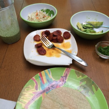 Yogurt-lime-cilantro sauce, shredded cabbage, avocado, longaniza, and corn tortilla ready to be filled with delicious.