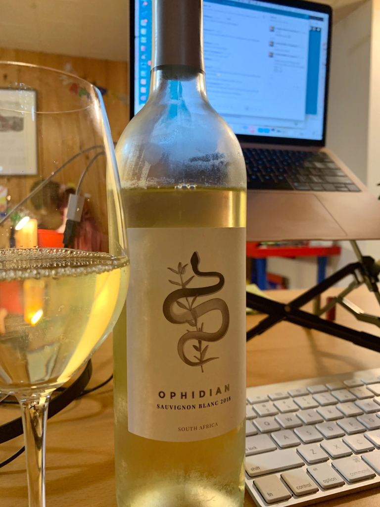 A photograph of Ophidian Sauvignon Blanc, next to a glass, in front of a computer.