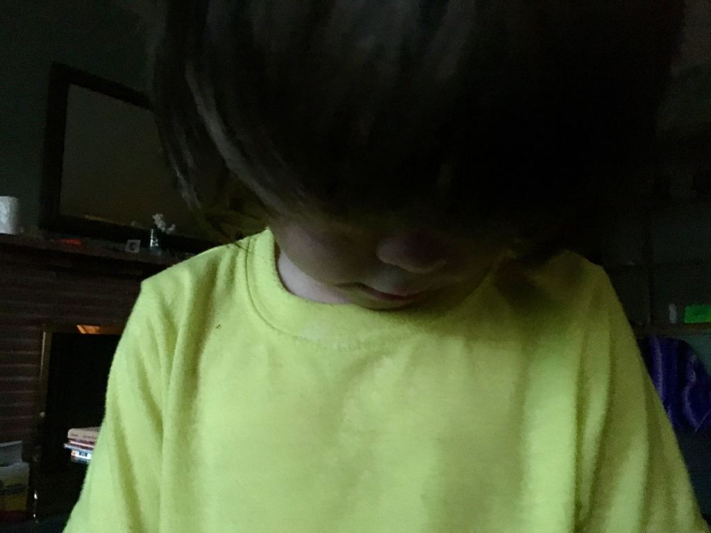 Image of a small dejected child, head lowered, with hair covering face. Child is wearing a fluorescent yellow shirt. Image is very dark.