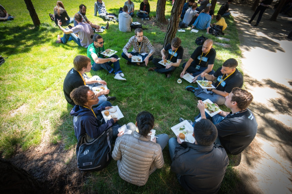 A group of conference attendees, sitting in a circle, with plates of food in their laps, in a grassy space.
